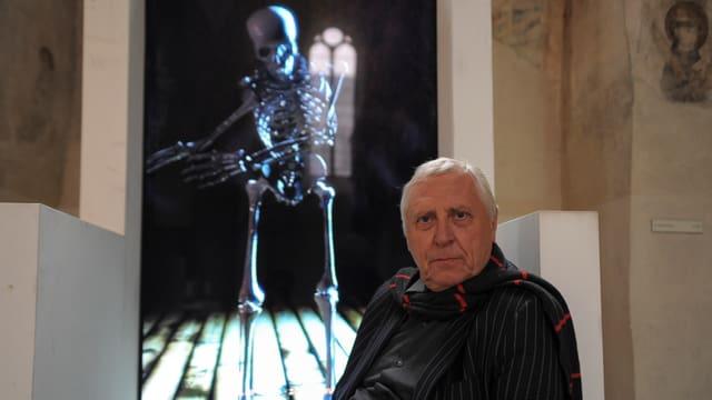 Peter Greenway sitzt vor einer seiner Projektionen, auf denen ein tanzendes Skelett erscheint.