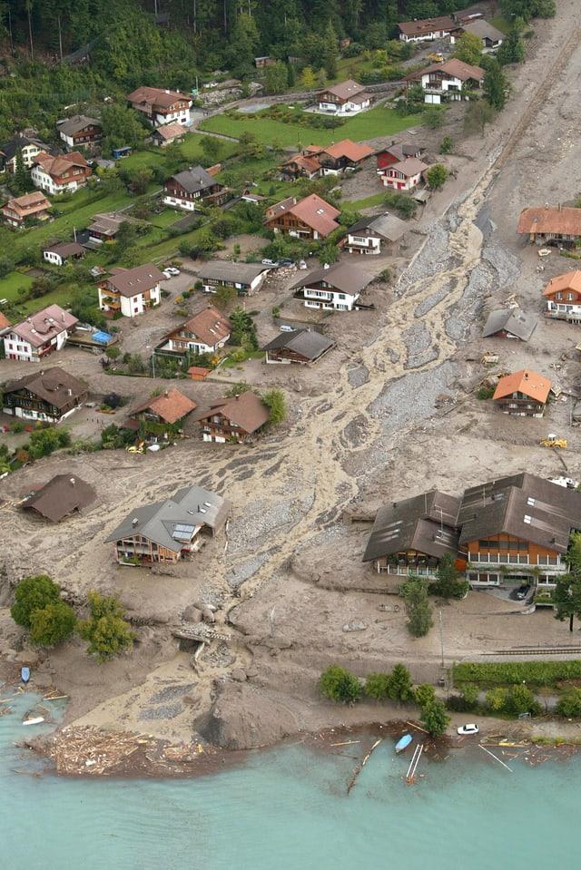 Luftbild vom Seeufer. Wiesen und Häuser sind mit Dreck überflutet und teilweise weggespühlt.