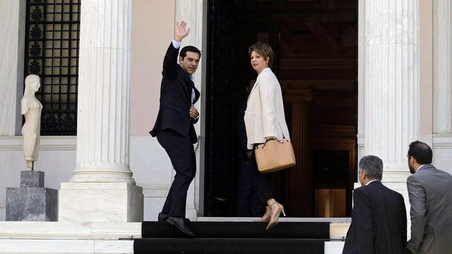 Tsipras und Regierungssprecherin Olga Gerovasili gehen Stufen zwischen zwei Säulen hoch, blicken zurück und er winkt.