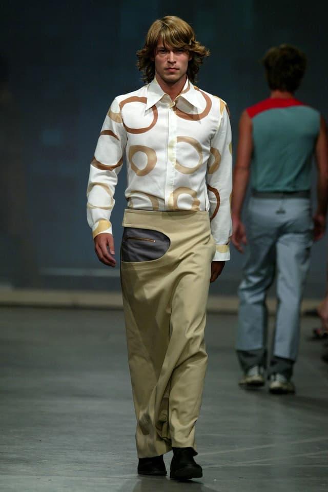 Ein männliches Model geht mit einem langen Rock übe den Laufsteg.