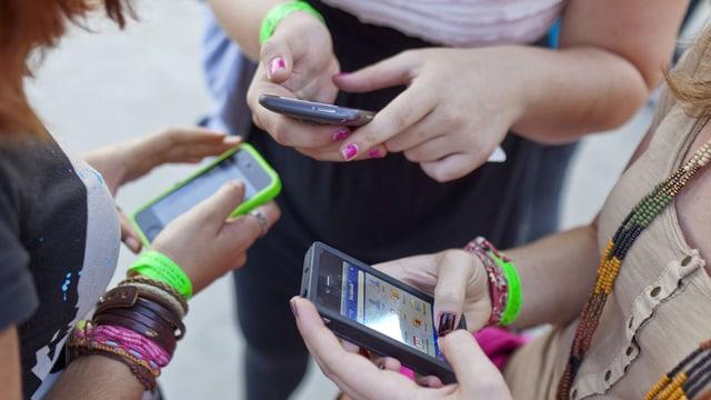 Die Hände dreier Mädchen, die je ein Smartphone halten.