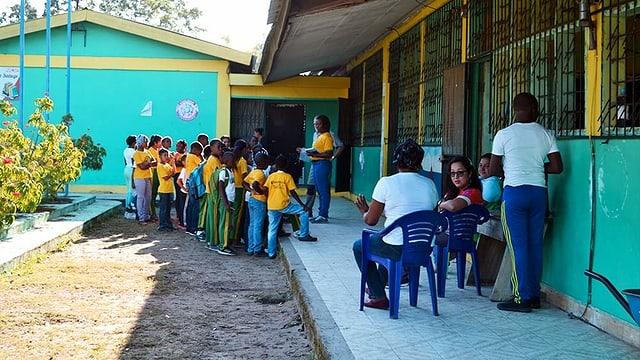 eine Schule, wo die Kinder draussen stehen