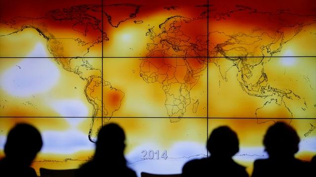 Teilnehmer der Pariser Klimakonferenz vor eine Weltkarte mit aussergewöhnlichen Wetterereignissen