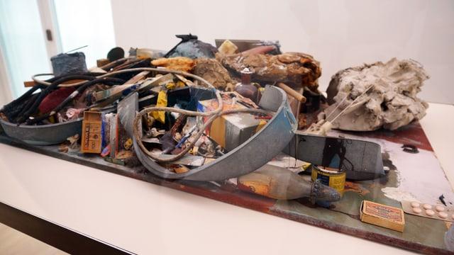Alte Schachteln, Eisenteile und Kabel auf einem Ausstellungstisch.