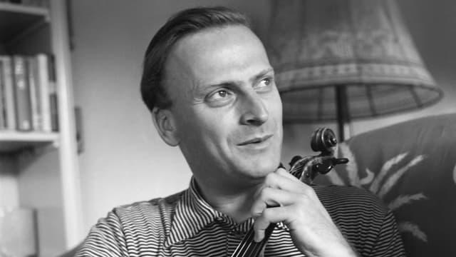 Schwarzweissfoto: Yehudi Menuhin sitzt im Wohnzimmer, die Geige hält er wie ein Cello.