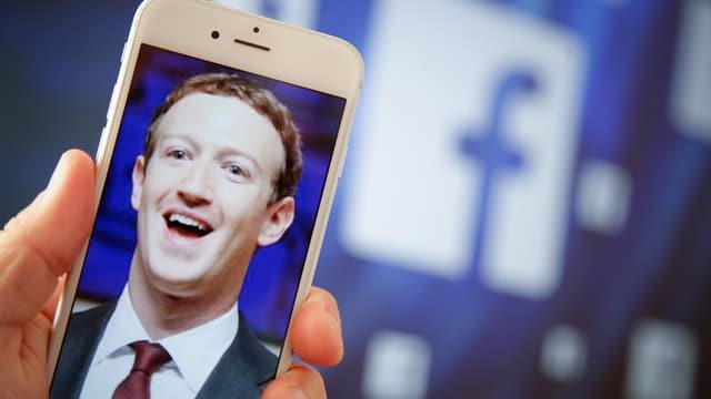Symbolbild: Aufnahme Zuckerbergs auf einem Handy vor einem grossen Facebook-Logo.