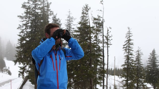Nik sucht mit dem Feldstecher etwas in der verschneiten Landschaft.