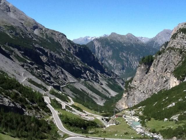 In einem klaren Bergsee spiegelt sich die Gebirgskulisse.