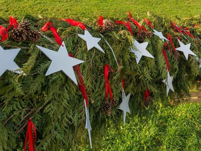 Adventskranz - mit Sternen und Tannzapfen geschmückt.