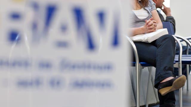 Eine unbekannte Frau wartet in einem Regionalen Arbeitsvermittlungszentrum auf die Beratung.