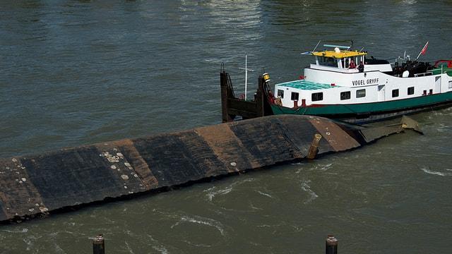 Der Rumpf des Kranschiffes Merlin ragt aus dem Rhein. Daneben ist das Lastschiff Vogel Gryff zu sehen.