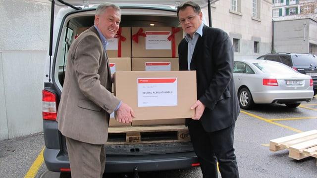 Zwei Männer verladen Kartonkisten in ein Auto.