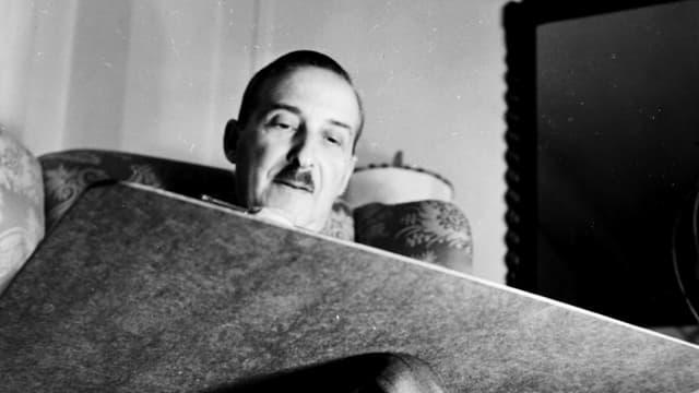 Ein Mann sitzt in einem Stuhl mit einem Schreibbrett auf dem Schoss.