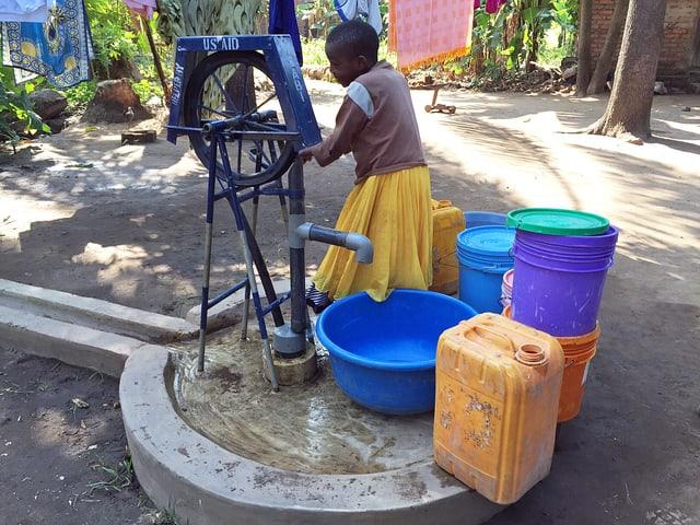 Eine Frau betätigt eine Handpumpe und füllt verschiedenste farbige Plastikgefässe mit Wasser.