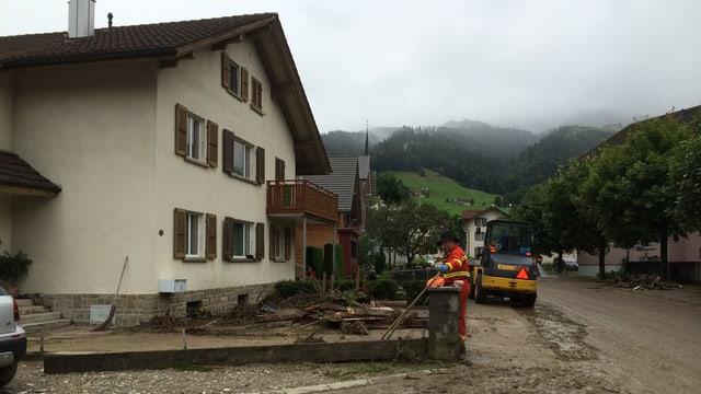 Ein beschädigtes Haus im Hintergrund und Schlamm auf der Strasse davor.