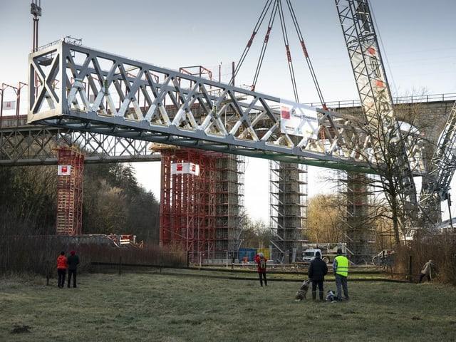Die Stahlbrücke wird auf ein Gerüst gehoben.