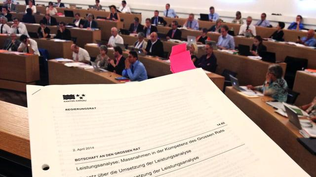 Unterlagen der Debatte im Vordergrund, die Ratsmitglieder im Hintergrund.
