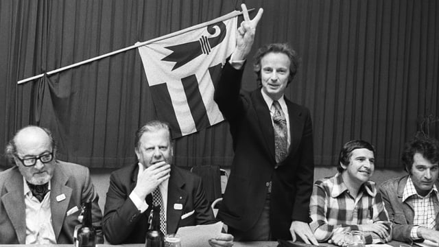 Mehrere Männer sitzen an einem Podiumstisch, ein Mann steht und zeigt das Victory-Zeichen.