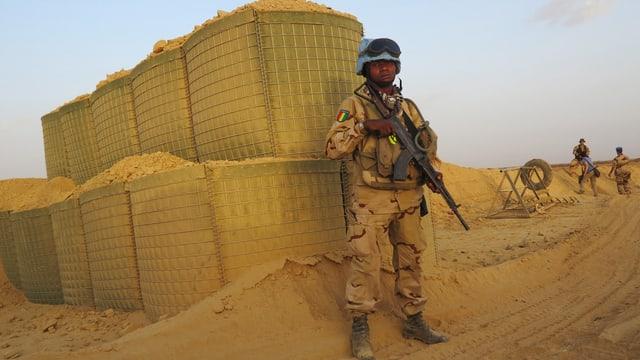 Schwarzer Blauhelm-Soldat steht im Wüstensand Wache bei einem UNO-Stützpunkt in Mali, Archivbild vom Juli