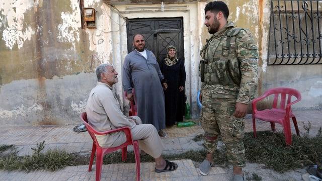 Ein von der Türkei unterstützter syrischer Soldat spricht mit älteren Menschen in Tal Abjad.