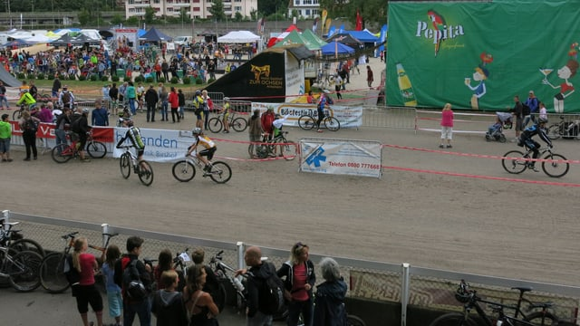 Die Sandbahn des Schänzli mit Bikern, die sich für ihr Rennen einfahren. Im Hintergrund die Zeltstadt mit, rechts ein Teil der Sprungrampe.