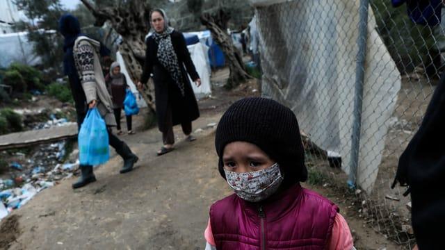 Menschen in Moria, im Vordergrund ein Kind mit Gesichtsmaske.