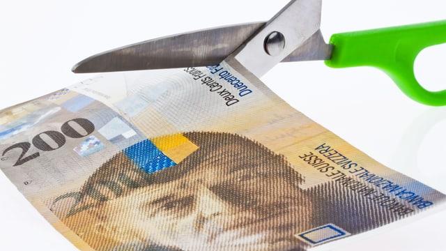 Eine Schere schneidet in eine 200-Franken-Note