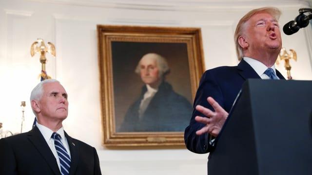 Pence steht hinter Trump, der in ein Mikrofon spricht.