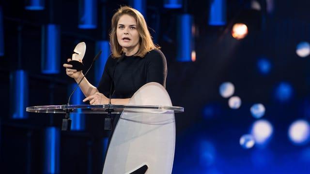 Junge Frau an einem Rednerpult mit Trophäe in der Hand.