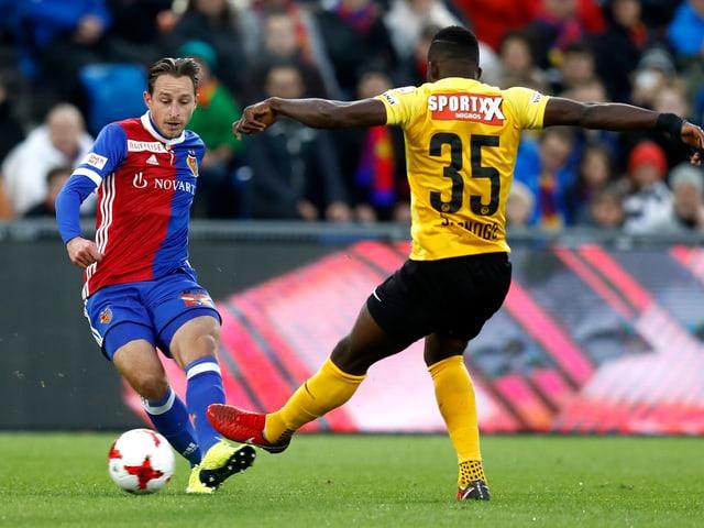 Ein Basel-Spieler spielt den Ball, ein YB-Spieler versucht ihn zu stören.