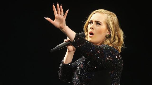 Adele singend bei einem Konzert.