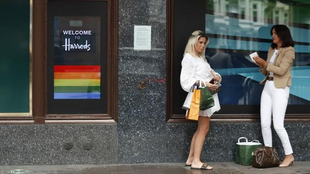 Zwei Frauen stehen vor einem Geschäft.