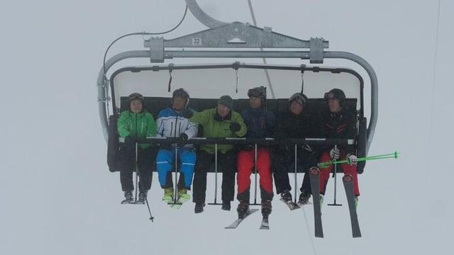 Ein Sessellift mit sechs Skifahrern drauf.