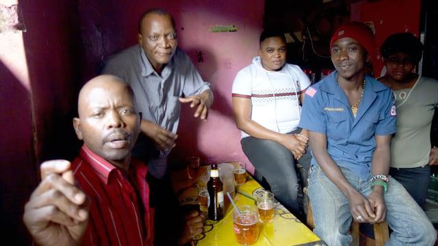 Schwarze Männer beim Biertrinken in einer Bar.