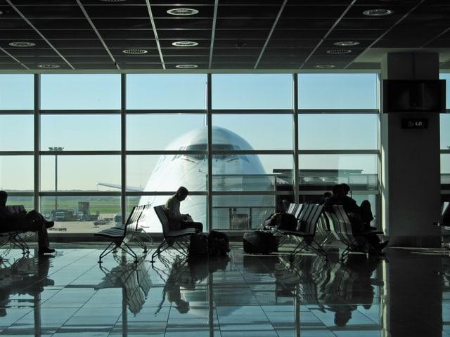 Vor einem Gate in einem Flughafen warten Reisende aufs Boarding.