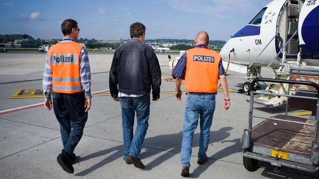 Zwei Polizisten mit oranger Schutzweste begleiten einen Mann in schwarzer Lederjacke zu einem wartenden Kleinflugzeug.