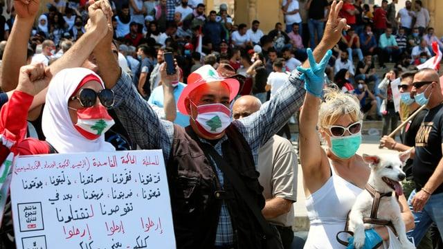 Demonstrantinnen und Demonstranten mit Transparent, manche tragen eine Gesichtsmaske.