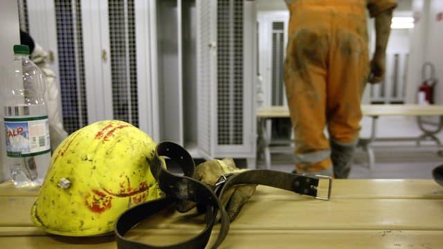 Umkleidekabine auf Baustelle: Mineralwasserflasche, gelber Helm und ein Ledergürtel auf einer Bank.