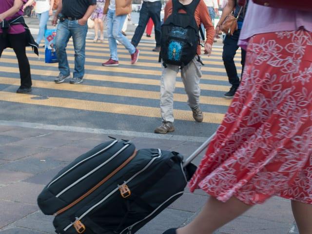 Ein Frau mit Rollkoffer, dahinter ein Zebrastreifen in der Luzerner Innenstadt