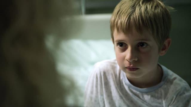 Ein traumatisierter Junge schaut einer Psychologin in die Augen.