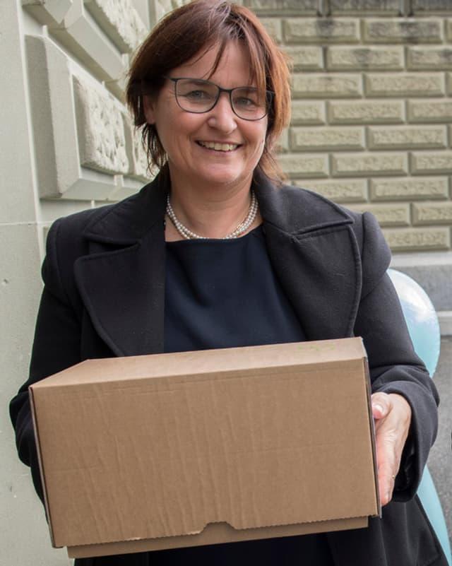 Marina Carobbio mit einer Kartonschachtel.