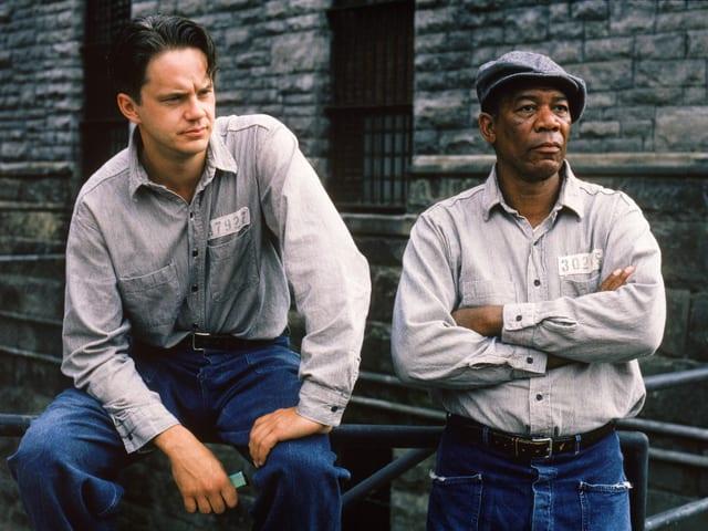 Zu sehen sind die Schauspieler Tim Robbins und Morgan Freeman in einem Gefängnishof. Sie tragen Sträflings-Kleidung. Ein Hemd mit einer Gefangenen-Nummer.