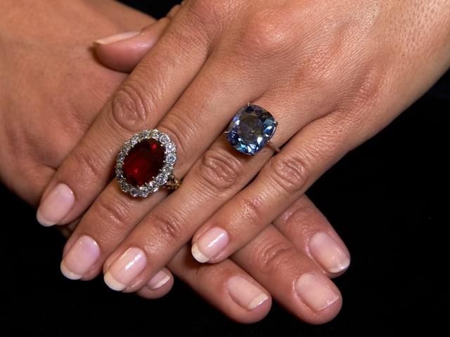 Hand mit zwei Diamantringen
