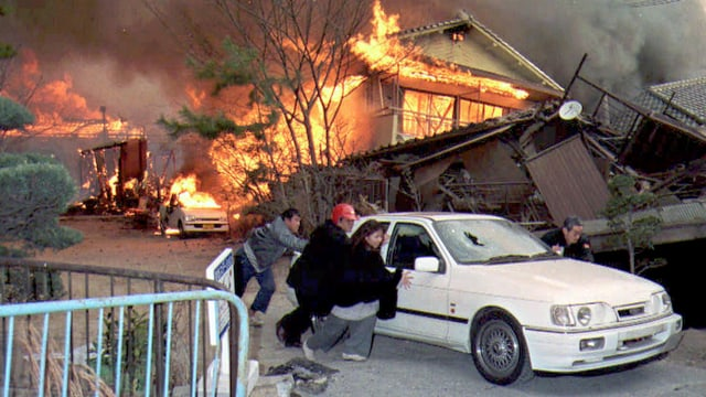 Menschen vor einem brennenden Haus