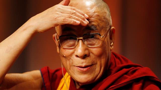 Der Dalai Lama hält sich die Hand über die Stirn, weil er geblendet wird
