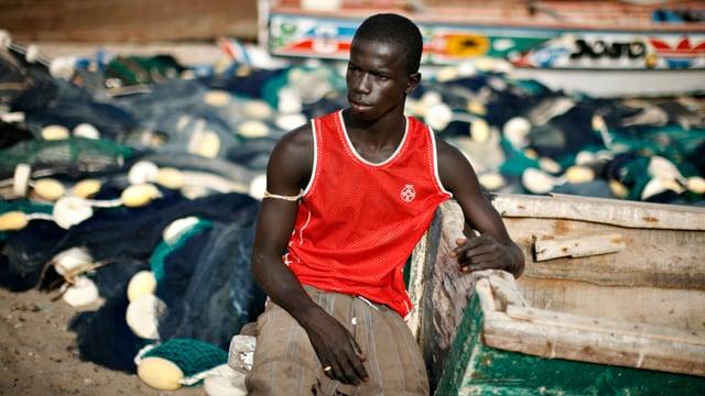Ein junger Mann sitzt neben einem Fischerboot.