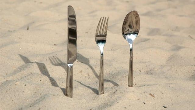 Messer, Gabel und Löffel stecken in Sand.