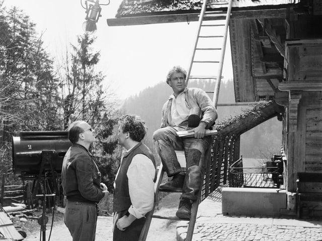 Schnyder und zwei Schauspieler befinden sich auf einem Hof in den Bergen.