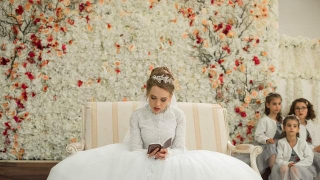 Ein junge Braut liest in einem Büchlein.