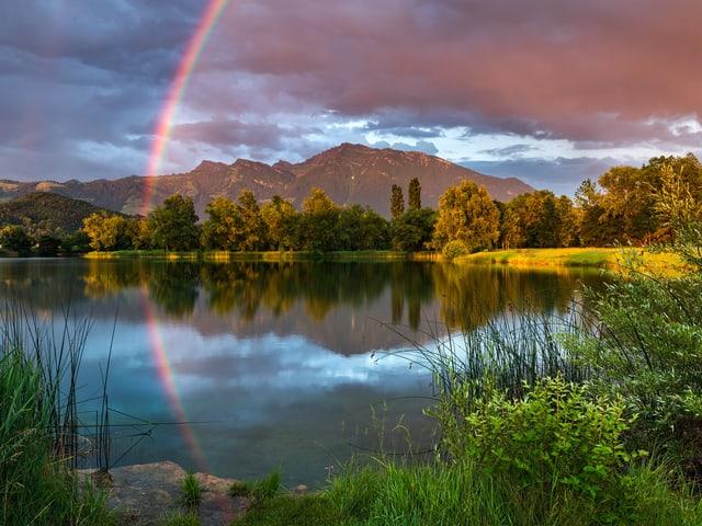 Regenbogen spiegelt sich im See.